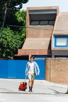 Homem moderno com saco de bagagem andando na rua