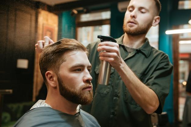 Homem moderno cortando cabelo de cabeleireiro enquanto está sentado na cadeira.