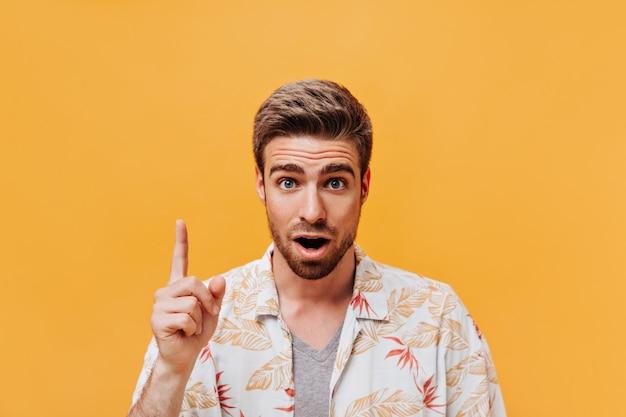 Homem moderno de olhos azuis com penteado descolado e barba ruiva em roupas da moda estampadas de verão, tendo uma ideia e olhando para a câmera