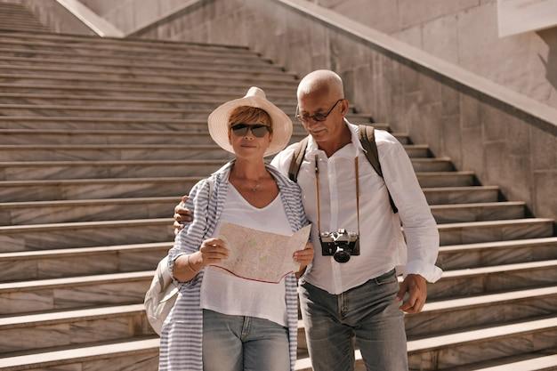 Homem moderno em óculos, camisa branca e calça jeans com a câmera abraçando a esposa de chapéu em blusa listrada