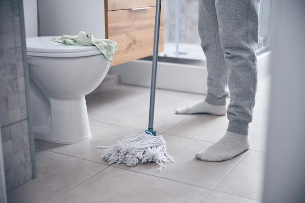 Homem moderno em pé no chão em frente a um vaso sanitário de cerâmica