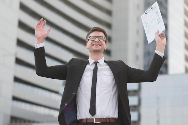 Homem moderno feliz de baixo ângulo com prancheta