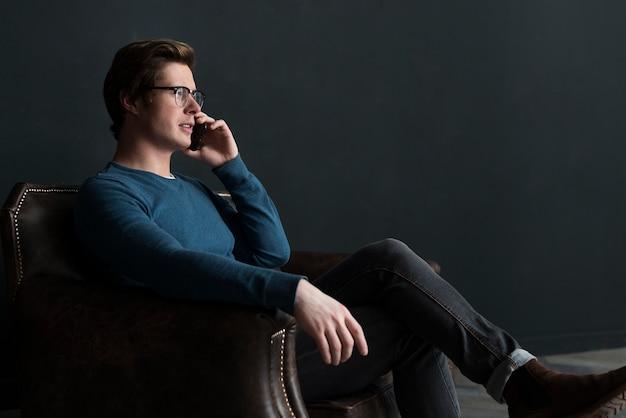 Homem moderno lateralmente falando ao telefone
