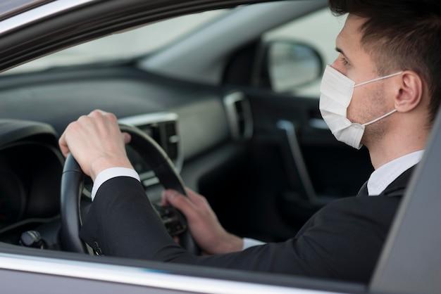 Homem moderno no carro com máscara