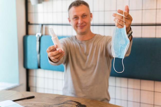 Homem moderno segurando uma máscara médica e um desinfetante