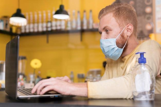 Homem moderno trabalhando usando máscara médica