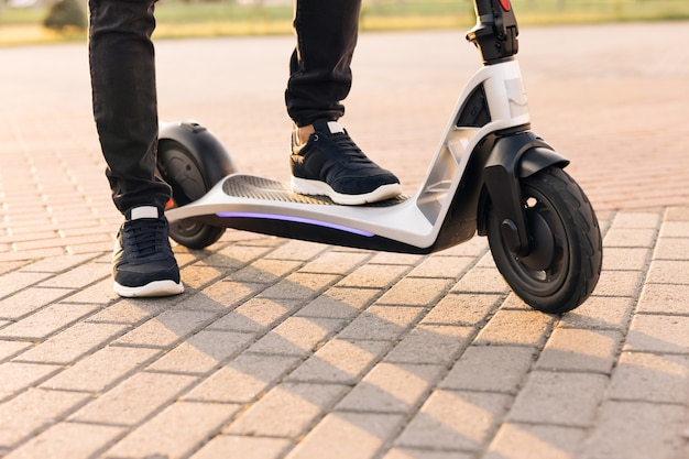 Homem moderno usando scooter elétrico em dia ensolarado homem adulto andando de scooter elétrico para trabalhar