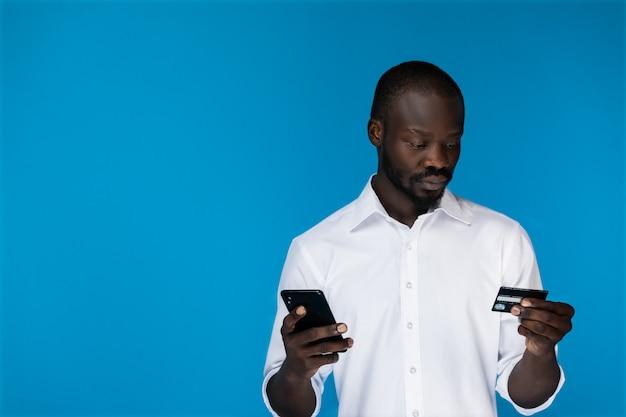 Homem moderno usando um cartão de crédito com um telefone