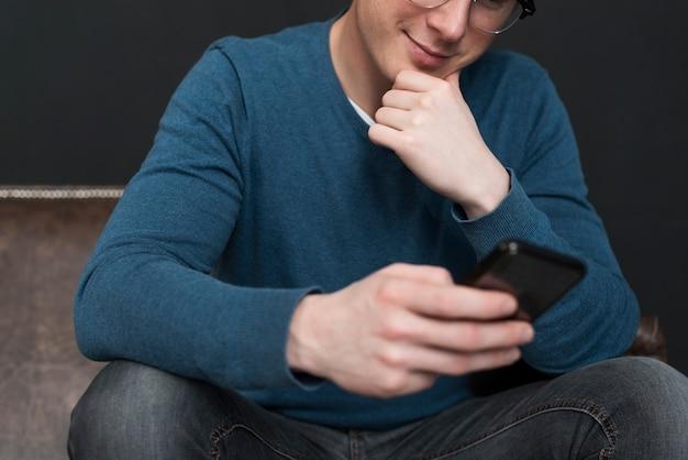 Homem moderno, verificando as mídias sociais em seu telefone close-up
