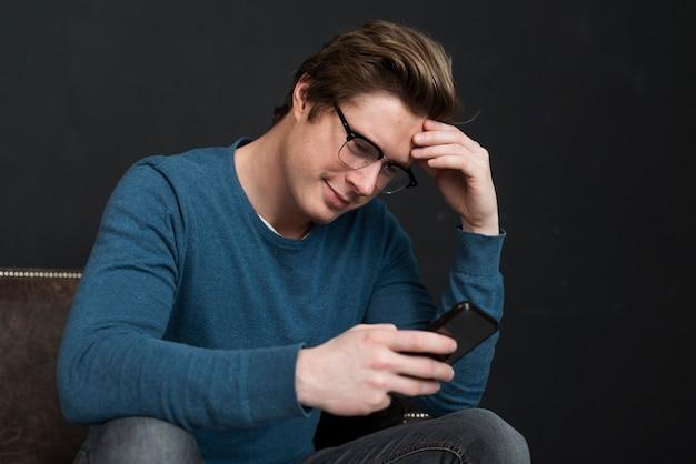 Homem moderno, verificando as mídias sociais em seu telefone