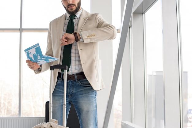 Homem moderno, verificando o tempo no aeroporto