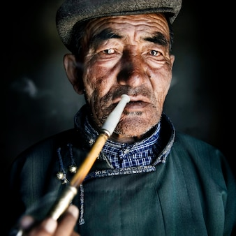 Homem mongol no vestido tradicional, fumando um cachimbo.