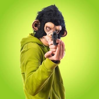 Homem monkey atirando com uma pistola em fundo colorido