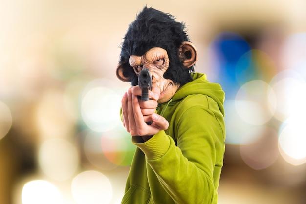 Homem monkey que dispara com uma pistola no fundo desenfocado