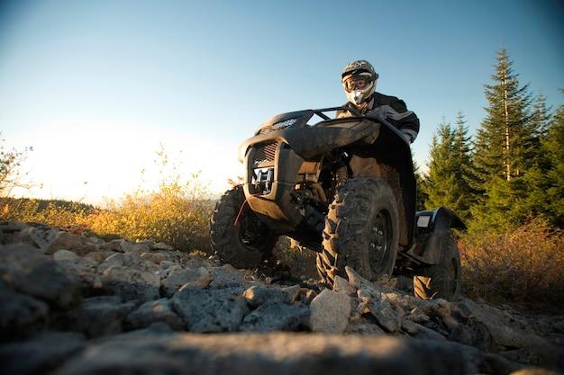 Homem, montando, atv, cima, colina rochosa