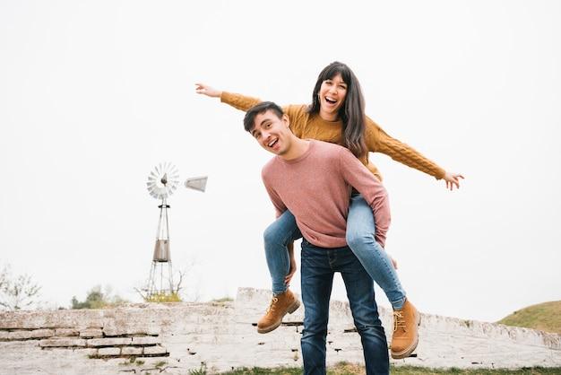 Homem, montando, rir, mulher, piggyback, tendo divertimento, em, natureza