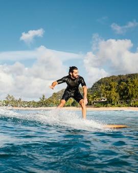 Homem montando sua prancha de surfe e se divertindo, tiro vertical