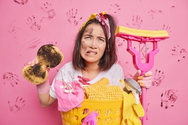 Homem morde lábios parece descontente para cima manchado de sujeira segura a esponja e o esfregão usa equipamento de limpeza para arrumar poses do quarto em rosa