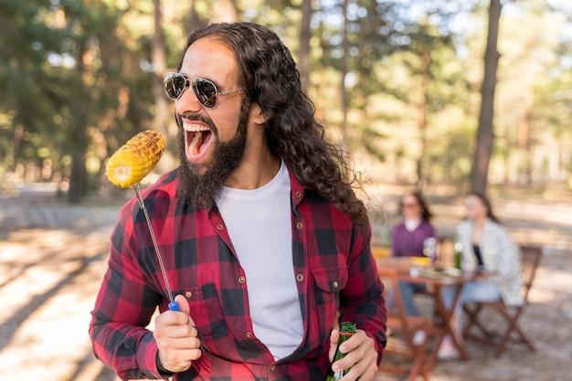 Homem mordendo milho torrado ao ar livre