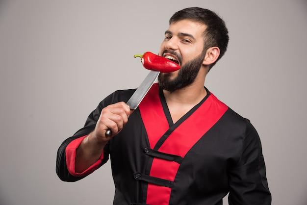 Homem mordendo uma pimenta vermelha na faca.