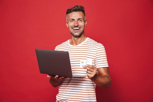 Homem morena com camiseta listrada sorrindo enquanto segura o cartão de crédito e o laptop isolado no vermelho