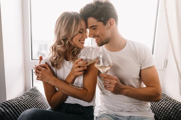 Homem moreno abraçando a namorada e bebendo champanhe. casal de família comemorando aniversário.