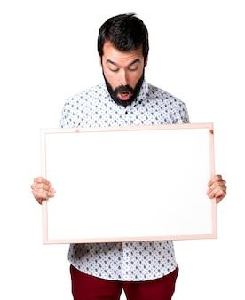 Homem moreno bonito com barba segurando um cartaz vazio
