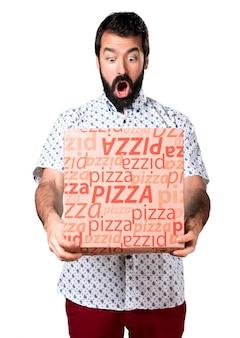 Homem moreno bonito com barba segurando uma pizza