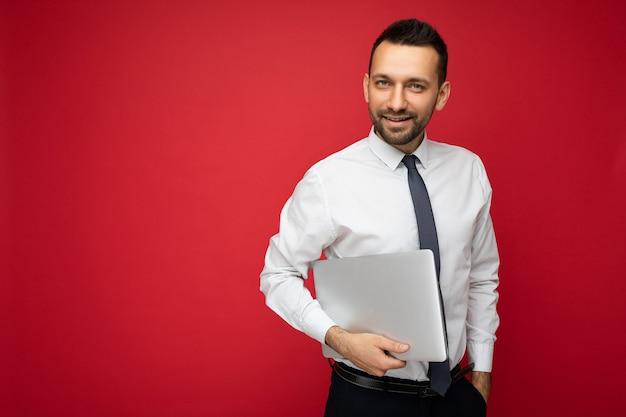 Homem moreno bonito segurando o computador portátil, olhando para a câmera, de camisa branca e gravata em vermelho isolado.