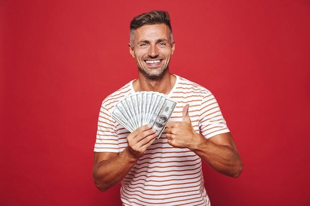 Homem moreno com camiseta listrada sorrindo e segurando um leque de dinheiro em dinheiro isolado no vermelho