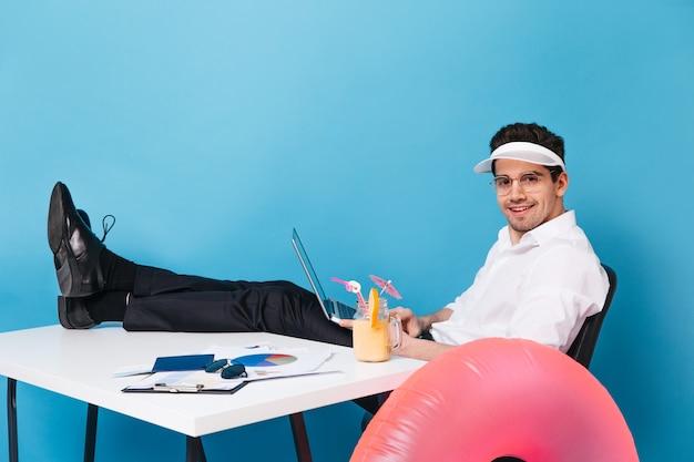 Homem moreno com chapéu e roupa de escritório está sentado com as pernas na mesa. cara segura laptop e trabalha enquanto desfruta de um coquetel em um espaço isolado com um círculo inflável.