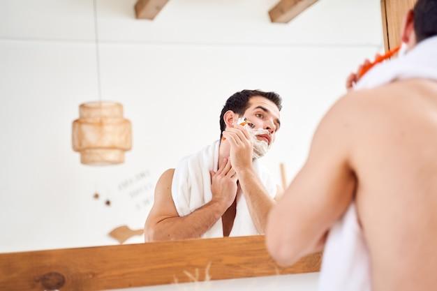 Homem moreno com espuma na barba faz a barba perto do espelho pela manhã