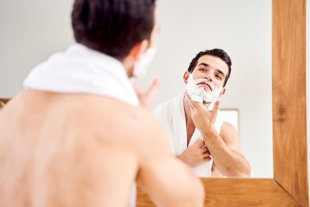 Homem moreno com espuma na barba perto do espelho pela manhã