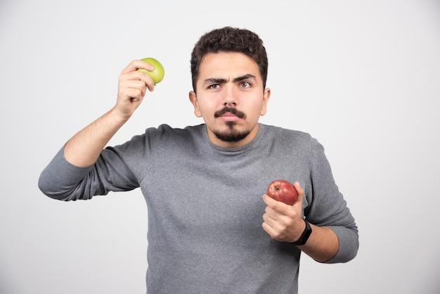 Homem moreno com maçãs em pé cinza.
