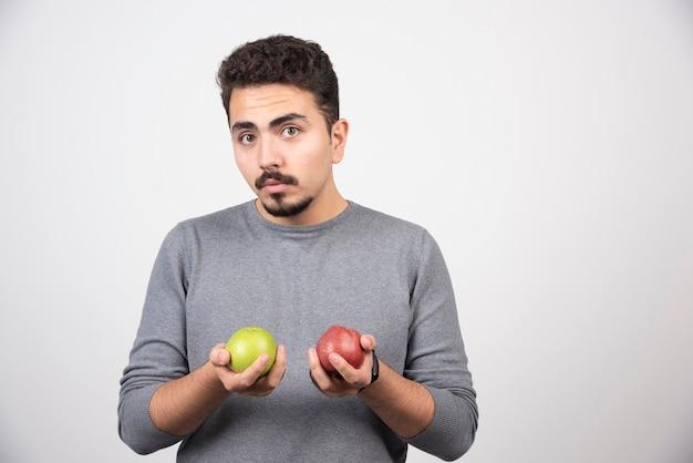 Homem moreno com maçãs posando em cinza.
