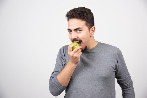 Homem moreno comendo maçã verde.