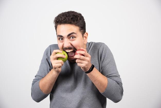 Homem moreno comendo maçãs verdes e vermelhas.