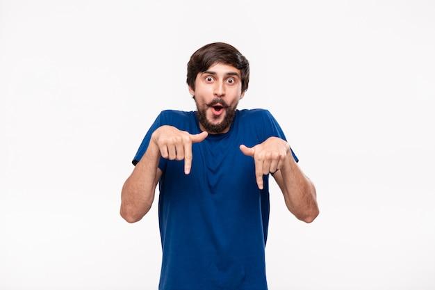 Homem moreno considerável em uma camisa azul com barba e bigodes apontando com os dedos para baixo em pé isolado. local do produto e propaganda.