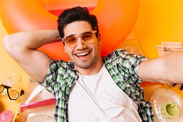 Homem moreno engraçado de camiseta branca e óculos faz selfie no colchão inflável.