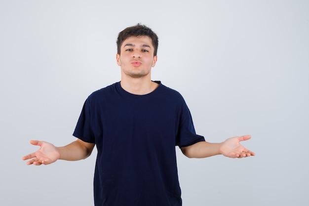 Homem moreno espalhando as palmas das mãos de lado na t-shirt e olhando alegre, vista frontal.