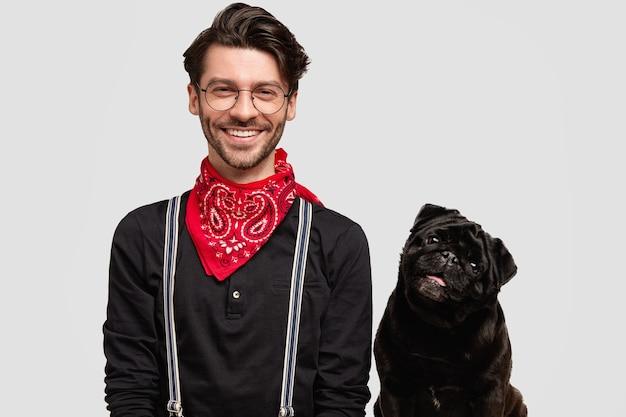 Homem moreno estiloso com lenço vermelho ao lado do cachorro