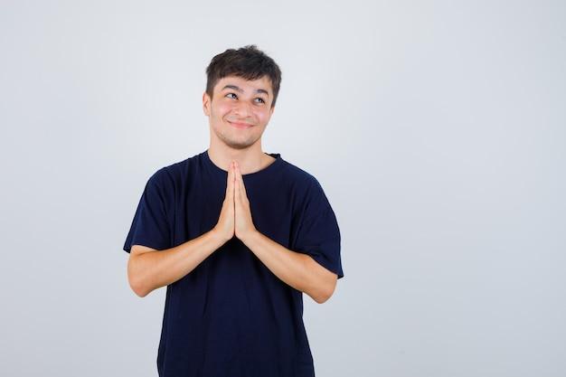 Homem moreno mostrando gesto namastê em camiseta escura e olhando curioso, vista frontal.