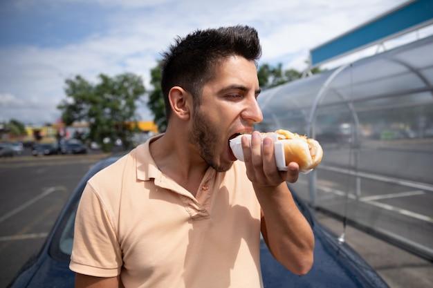 Homem moreno novo considerável bonito que come o cachorro quente no parque de estacionamento perto do posto de gasolina.