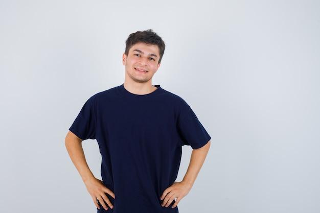 Homem moreno posando com as mãos na cintura em t-shirt e olhando alegre, vista frontal.