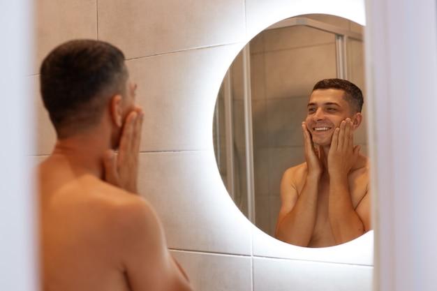 Homem moreno positivo feliz em pé no banheiro, olhando seu reflexo no espelho, tocando suas bochechas, aplicando agente de barbear no rosto, sorrindo.