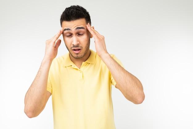 Homem moreno sente uma forte dor de cabeça e mantém a cabeça nas mãos em um fundo branco do estúdio.