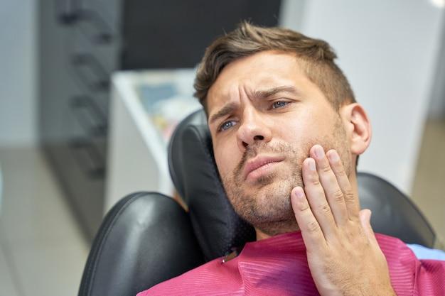 Homem moreno sofrendo de dores de dente na clínica