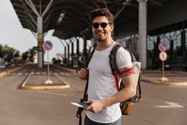 Homem moreno viajante com camiseta branca e óculos escuros sorrindo perto do aeroporto