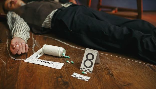 Homem morto e frasco de comprimidos na cena do crime, envenenamento por drogas