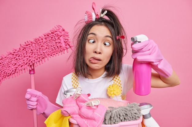 Homem mostra a língua cruza os olhos faz careta e brinca enquanto a limpeza da casa segura o detergente e o esfregão fica perto de uma pilha de roupas para lavar posa em rosa